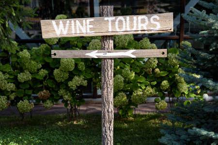Bois signe tournée de vin avec une flèche avec des arbustes verts sur fond
