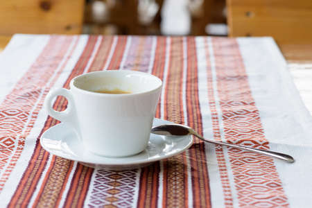 Photo of white cup of coffee with foam on a traditional restaurant table in Moldova, tablecloth with ornaments