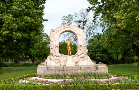 Photo of golden johann strauss statue at stadpark at sunset in vienna, austria Stock Photo