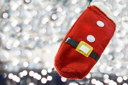 Photo of santa claus red glove over background with light bokeh dots, shallow depth of field
