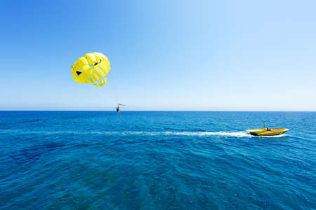 Photo of sea in protaras, cyprus island with yellow parasailing with people in shape of a skull with black eyes and a boat, immaculate blue water and sky