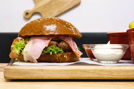 encurtidos: Delicious hamburger, medium rare, with bacon and fried potatoes, ketchup and mayonnaise, salad and pickles, wood plate. Lateral view Foto de archivo