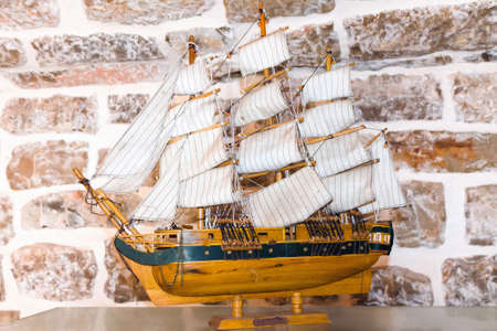 floreal: Miniature ship over brick background in museum near Budva, Montenegro, wooden replica of the old vessel sailfish