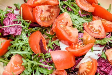 Close up photo of green healthy salad with ruccola and tomatoes Stock Photo