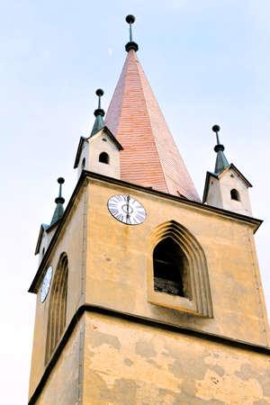 mid distance: Hungarian catholic church tower with clock, targu mures, romania