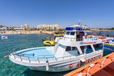 PROTARAS, CYPRUS - JUNE 16, 2016: Tourists on white aphrodite cruise boat with cyprus flag, at the pier, sea shores and hotels