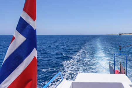 Norway flag and view from a white boat tail, white foam on immaculate water, protaras, cyprus island