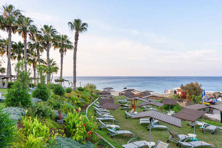 Hotel relaxing zone with palm trees and sea view in protaras, cyprus island, sunset Stock Photo