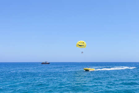 Sea view with people and black pirate boat, parasailing, immaculate waters, protaras, cyprus island, glide through the air wearing an open smile parachute while being towed by a motorboat