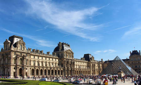 PARIS, FRANCE - SEPTEMBER 10, 2015: Louvre museum building, glass pyramida and people