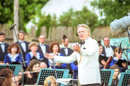 ORHEIUL VECHI, MOLDOVA - JUNE 08, 2017: Conductor Friedrich Pfeiffer performing at Descopera Butuceni Village open air music festival, symphonic orchestra of Moldova