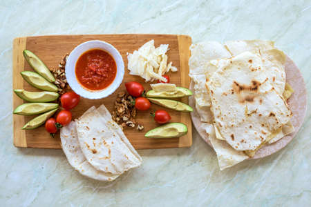 Wood plate with food, on a white table. Tomato, avocado, wallnuts and parmesan cheese with pita bread