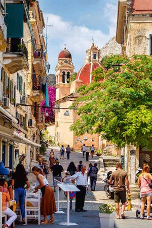 CORFU ISLAND, GREECE - JUNE 26, 2017: Narrow tourist street with people walking. Corfu city, Greece. Daylight view