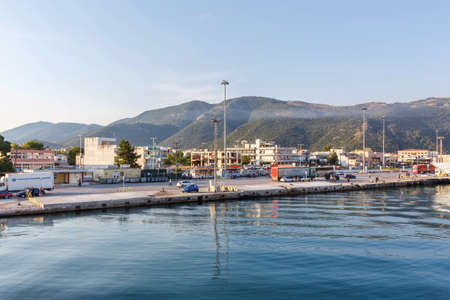CORFU ISLAND, GREECE - JUNE 26, 2017: View on port and green mountains of Greece, Corfu at sunset. Cars and people working