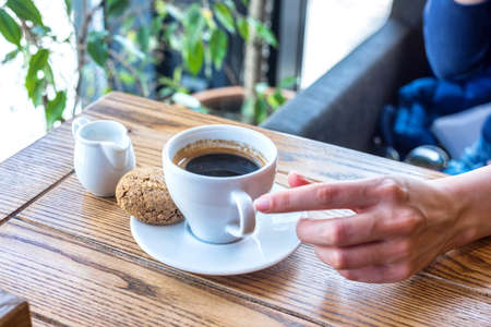 Coffee cup with cookie on wooden table in restaurant with view on window and plant. Woman touching cup with hands to drink.