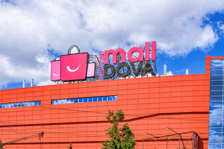 CHISINAU, MOLDOVA - JULY 14, 2017: Shopping centre malldova with red bags logo, blue sky and clouds, sky reflection on glass windows Editorial