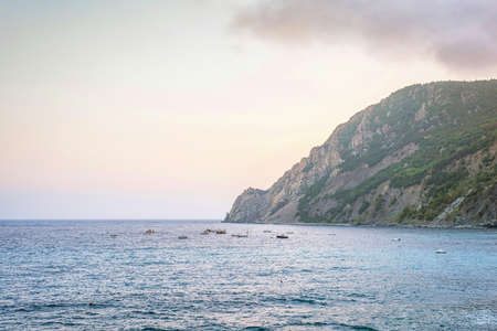 Sunset view to blue water and green mountains. Monterosso al Mare, Italy. Cinque Terre beauties