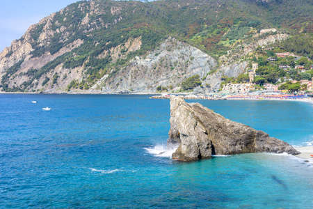 Daylight sunny day view to blue sea, rock in water and green mountains. Monterosso al Mare, Italy, Cinque Terre.