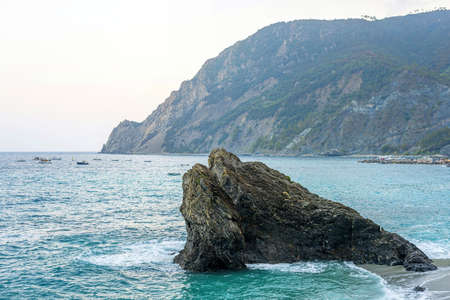 Beautiful view to rock in blue water and green mountains. Monterosso al Mare, Italy. Cinque Terre
