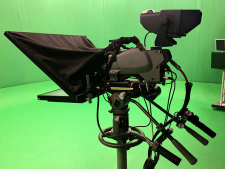 Modern empty green video recording and broadcasting studio with tv channel led screen and metalic stands, text prompter Stock Photo