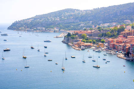 sur: Beautiful daylight view to boats and ships on water in luxury resort villefranche sur mer and bay on french riviera at mediterranean sea Cote dAzur in France. Stock Photo