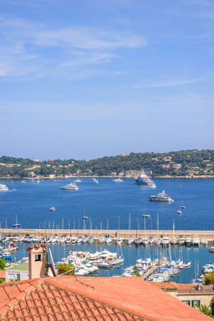 tropez: Beautiful daylight view to boats and ships on water in luxury resort villefranche sur mer and bay on french riviera at mediterranean sea Cote dAzur in France. Stock Photo