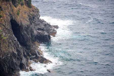 View from mountains to blue sea. Water smashing rocks. Monterosso al Mare, Cinque Terre, Italy