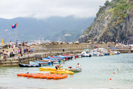 city park boat house: VERNAZZA, ITALY - JUNE 26, 2017: View to little port of city with parked boats and people walking