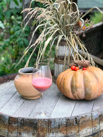 Daylight view to strawberry smoothie, pumpkin, dried hay and ceramic pot on old wine barrel, winery in Moldova