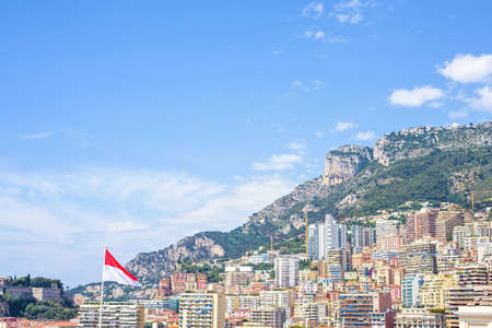 Daylight sunny view to tall city buildings and mountains. Bright blue sky with a few clouds on background. State flag blowing. Monaco, France, negative copy space