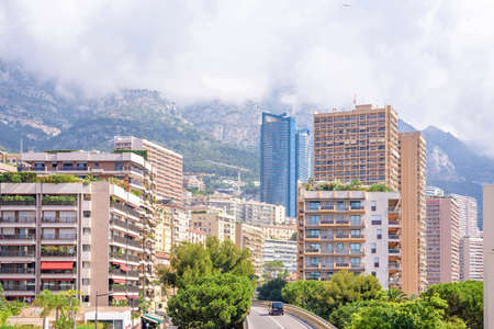 Beautiful daylight view to tall buildings and big green mountains in clouds on background. Cars riding on bridge. City of Monaco, France