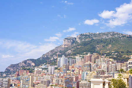 Daylight sunny view to city buildings and mountains. Bright blue sky with a few clouds on background. Monaco, France, negative copy space