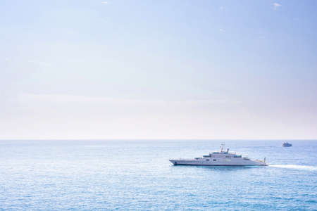 Daylight sunny view to yachts cruising on water. Monaco, France. Bright blue sky with a few clouds on background, negative copy space Foto de archivo