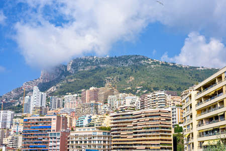 Daylight sunny view to city big buildings and mountains full of trees. Bright blue sky with a few clouds. Monaco, France Stock Photo