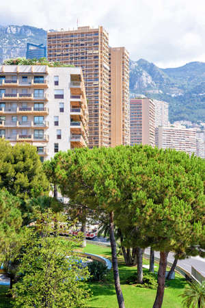 Beautiful daylight view to tall city buildings, green trees and big mountains. Bright blue sky with a few clouds on background. Monaco, France