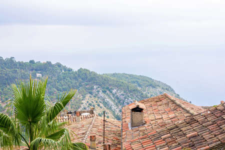 Daylight foggy view to Eze village medieval house, trees and mountains from castle. Beauties of French Riviera