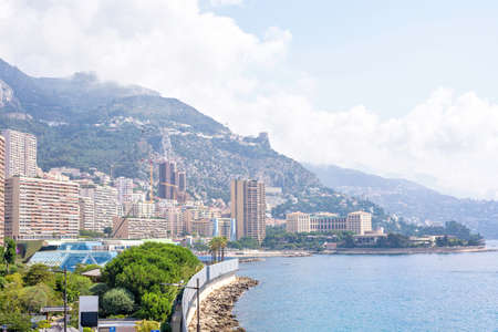 Beautiful daylight view to Monaco city big buildings and sea in France. Big green mountains and bright blue sky with clouds on background.