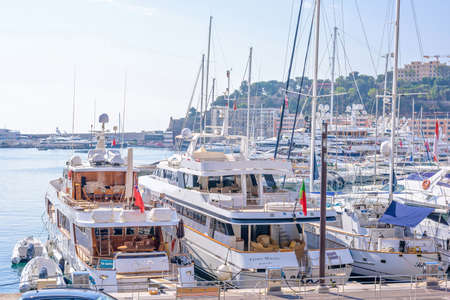 MONACO, FRANCE - JUNE 28, 2017: Daylight sunny view to parked luxury yachts and tall buildings constructed on hill. Bright blue clear sky