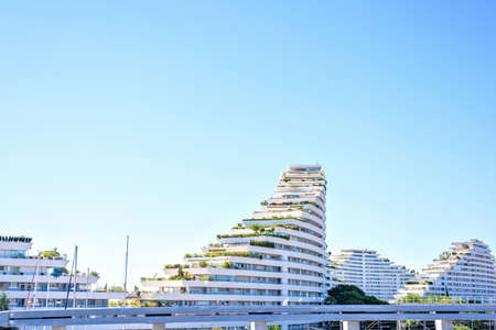 Daylight sunny view from side to ship shaped apartments. Bright blue clear sky on background. View from highway. Cagnes-sur-mer, France. Stock Photo