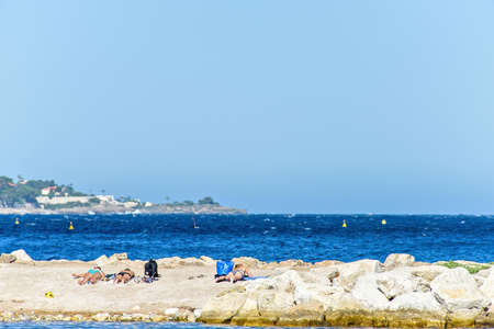 Daylight view to people relaxing and sun tanning on sand near rocks. Bright blue clear sky. Island with buildings and trees on background. Negative copy space, place for text. Cap dAil, France