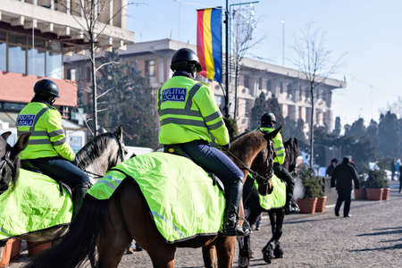 Local police in green uniform and helmet on horses patrolling on the main street in Iasi at the national day of unification of Romania