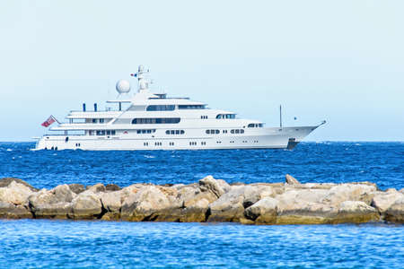 Daylight close-up view to white yacht cruising on water and splitting rocks. Bright blue clear sky. Negative copy space, place for text. Cap dAil, france