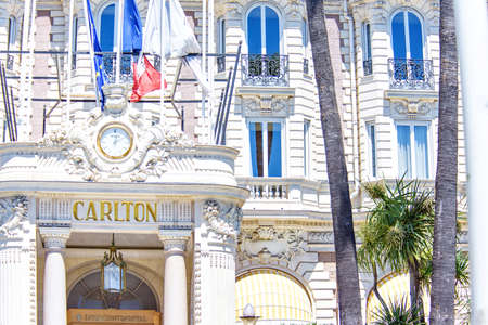 CANNES, FRANCE - JUNE 29,2017: Daylight view to Carlton hotel ornamented entrance with Rolex watch and balconies with tall windows.