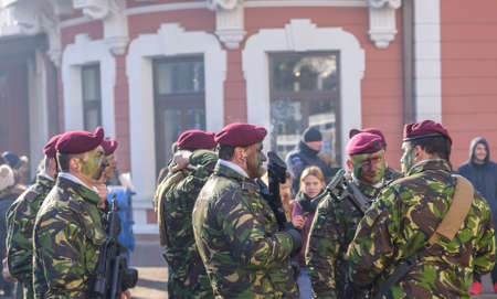 IASI, ROMANIA - JANUARY 24, 2018: Soldiers in military green camouflage uniform with automatic guns marching and celebrating in formation on the main street at the of Romania
