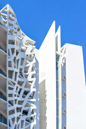 MONTE CARLO, MONACO - JUNE 29, 2017: Daylight view from bottom to latticed facade of Simona Tower Block by Jean-Pierre Lott. Luxury apartments in skyscraper. Negative copy space, place for text