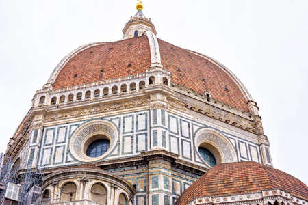 Daylight cloudy day view from bottom to ornamented facade of Cathedral Saint Mary of the Flower. Florence, Italy