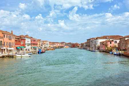 Daylight view to Venetian Lagoon and parked boats. People walking on sidewalk near colorful historic architecture buildings. Murano Island, Venice, Italy