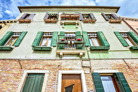 Daylight view from bottom to historic architecture building with green facade and balconies. Bright blue sky with clouds. Murano Island, Venice, Italy
