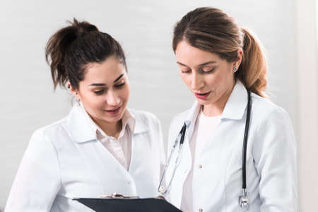 Two female assistants dressed in white coats talking to each other in the dentistry center. White and blured background. Healthcare idea