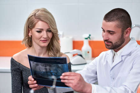 Caucasian male dentist explaining to female patient the x-ray in dental cabinet